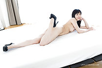 Lying on her front nude on bed in black high heels