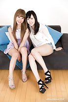 Girls seated on sofa knees pressed together wearing high heels