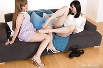 Reclining on sofa knees drawn up bare feet girlfriend looking down in high heels